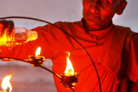 A monk lighting votive candles, Kataragama, Sri Lanka