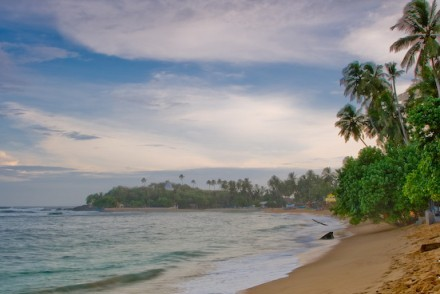 Attractive bay with golden sandy beach and waves for surfing, Unawatuna, Sri Lanka