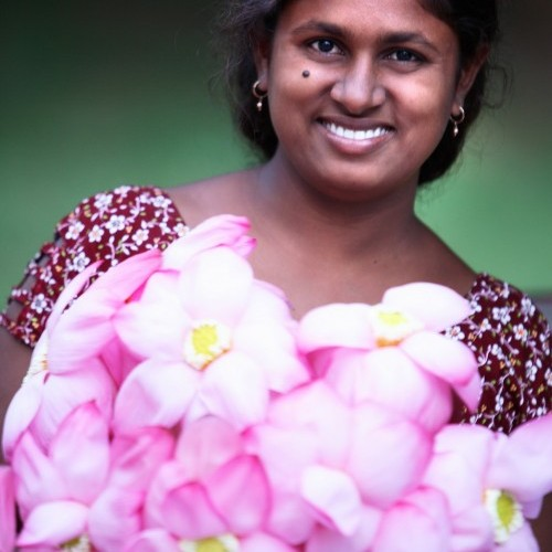 Pilgrim lady carrying votive Frangipani flowers, Kataragama, Sri Lanka